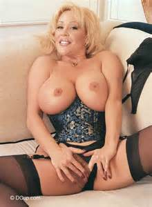 Big boobed blonde milf Kandi Cox in corset and stockings spreads her ...