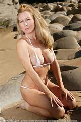 Classy blonde milf in tiny white bikini relaxes on the beach and shows ...